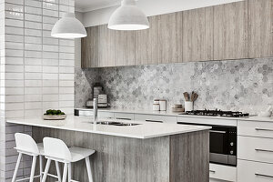 Modern kitchen in shades of grey and white with breakfast bar on island counter