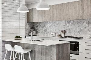 Moderne Küche in Grautönen mit Frühstückstheke an der Kücheninsel