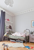 Vintage metal bed in child's bedroom with stucco ceiling frieze