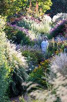 Frau geht durch naturnahen Sommergarten mit üppigen Stauden