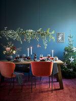 Girlande aus Eukalyptuszweigen überm festlich gedeckten Tisch