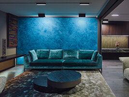 Elegante Lounge mit Designer-Sofas vor blauem Raumteiler in offenem Wohnraum