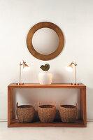 Holzkonsole mit Bambuskörben, Tischleuchten und Vase, darüber runder Wandspiegel