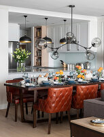 Festively set dining table, custom leather chairs and sculptural light fitting with glass lampshades