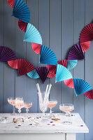Bunte Girlande aus Papierfächern als Partydeko über dem Buffet