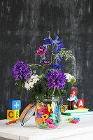 Blumen in einem Einmachglas mit bunten Buchstaben
