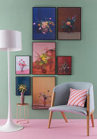 Floral artworks on green wall, standard lamp, side table and armchair
