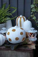 DIY Halloween decorations: white-painted pumpkins with glitter