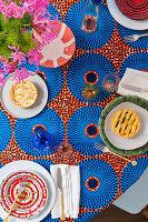 Rot und blau gemusterte Tischdecke und Tischsets, Keramikteller mit Törtchen