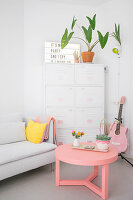 Sofa, white metal filing cabinet and pink coffee table and guitar