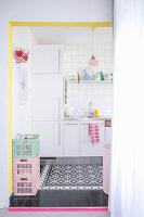 Blick in weiße Küche mit schwarz-weißem Fliesenboden und knallbunten Farbakzenten