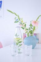 Blumen in hellblauer Vase davor Wasserflasche mit Gläsern auf Esstisch