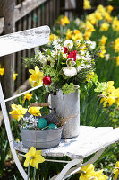 Natural spring bouquet on garden chair in bed of narcissus