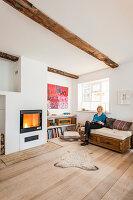 Helles Wohnzimmer mit Holzboden und Kamin, Frau auf Sofa sitzeend