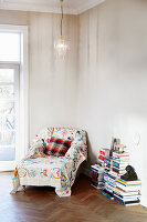 Colourful throw on chaise chair and stacks of books in corner