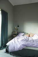 Rumpled bed in grey bedroom