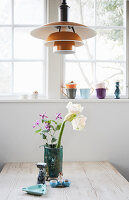 Vase of flowers on table below designer lamp in front of window