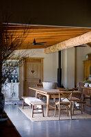 Holztisch mit Sitzbänken und Stühlen in rustikalem Esszimmer mit Holzbalken