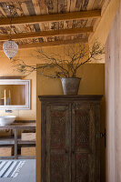Carved, rustic, wooden cupboard in front of washstand
