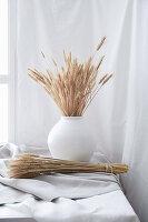 Strauß und Bund getrocknetes Getreide auf weißem Stoff