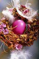 Easter nest decorated with pink flowers and feathers