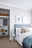 Double bed with button-tufted headboard against striped wallpaper and view into walk-in wardrobe