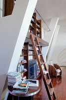 Bookcase with library ladder and fireplace in high-ceilinged room