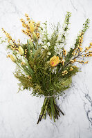 White and yellow bouquet of tulips, yellow berries, delphiniums and branches of mimosa