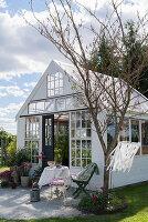 Idyllic summerhouse made from old windows in summery garden