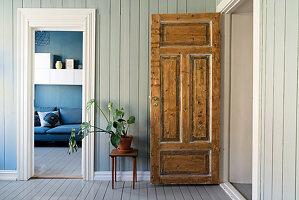 Rustikale Holztür, daneben Hocker mit Zimmerpflanze, Blick ins Wohnzimmer