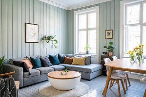 Graue Sofagarnitur, Couchtisch und Essbereich im Wohnzimmer mit hellgrün gestrichenen Holzwänden