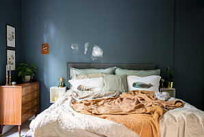 Double bed and retro chest of drawers in bedroom with grey-blue wall