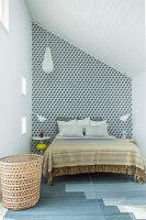 Doppelbett vor Wand mit Tapete im Schlafzimmer mit Dachschräge
