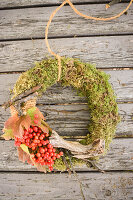 Moss wreath with viburnum berries and twigs on weathered wood