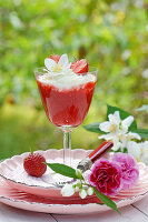 Strawberry compote in stemmed glass and flowers