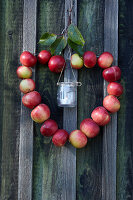 Heart-shaped wreath of apples with candle lantern