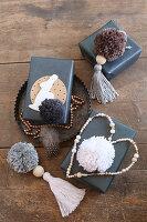 Schwarz verpackte Geschenke mit Pompons, Quasten und Perlenherz