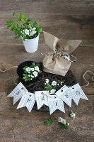 Girlande aus bedruckten Buchseiten, Blumen und eine Geschenktüte
