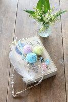 Pompons, Herz aus Perlen und Würfel auf einer alten Schachtel