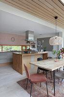 Esstisch mit Stühlen vor Küchentheke in offenem Wohnraum