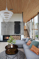 Grey sofa set and coffee tables in front of fireplace with firewood rack