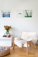 Armchair with fur rug and pouffe in front of low sideboard in living room