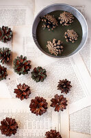 Dipping pine cones in green paint