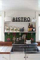 Sink with green tiled splashback below vintage storage tins on shelves in kitchen