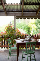 Dining table with green-painted wooden chairs on veranda