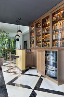 Luxurious bar with illuminated, glass-fronted cabinets and marble floor