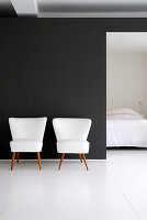 Two white retro armchairs against black wall with view into bedroom