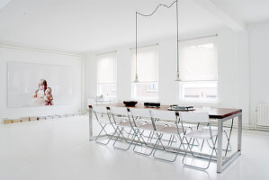 Folding chairs around long table in minimalist dining room with white floor
