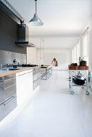 Open-plan kitchen in minimalist interior with white floor