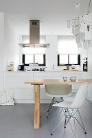 Zettel'z lamp above dining table in front of white, open-plan kitchen